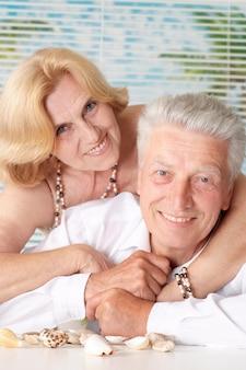 Casal de idosos com conchas descansando em casa