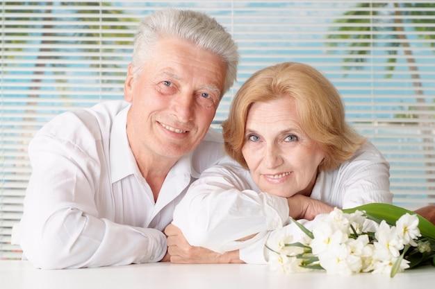 Casal de idosos com flores descansando em casa