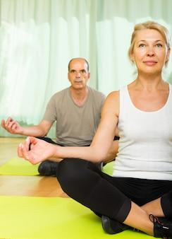 Casal de idosos com ioga em casa
