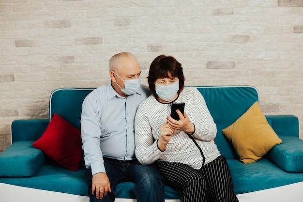 Casal de idosos com máscaras médicas, sentado no sofá em casa e tendo uma chamada de vídeo. quarentena.