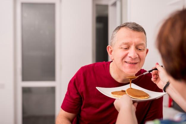 Casal de idosos comendo panquecas