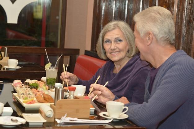 Casal de idosos comendo sushi em um café