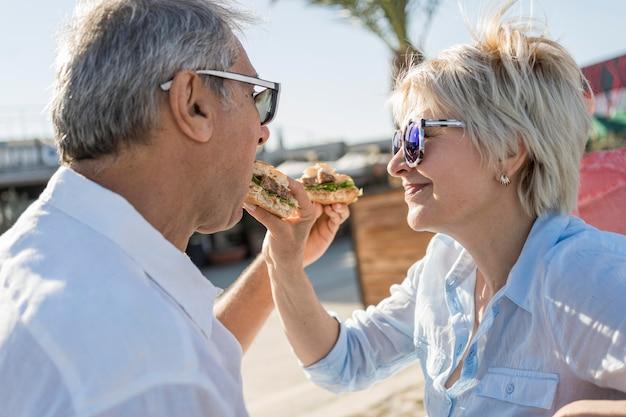Casal de idosos comendo um hambúrguer ao ar livre