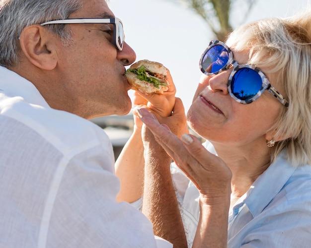 Casal de idosos compartilhando um hambúrguer ao ar livre