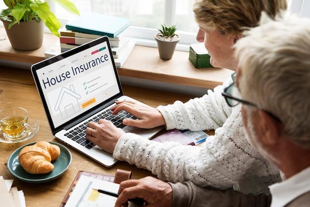 Casal de idosos consultando seguro residencial no laptop