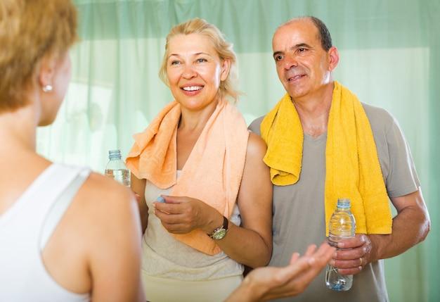 Casal de idosos conversando com treinador