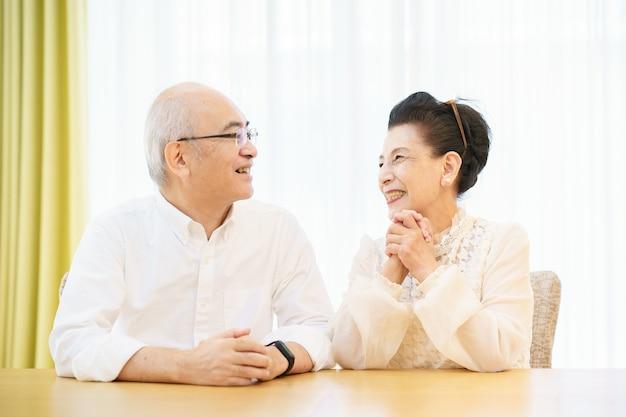 Casal de idosos conversando com um sorriso na sala de estar