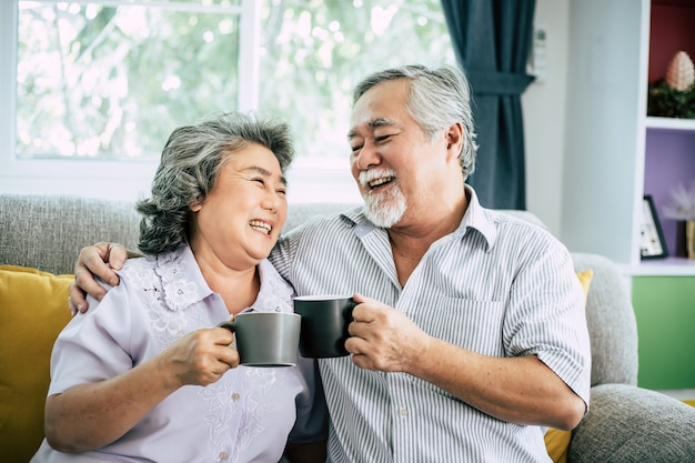 Casal de idosos conversando e bebendo café ou leite