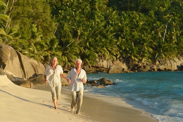 Casal de idosos correndo na praia perto do mar
