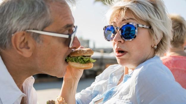 Casal de idosos curtindo um hambúrguer ao ar livre