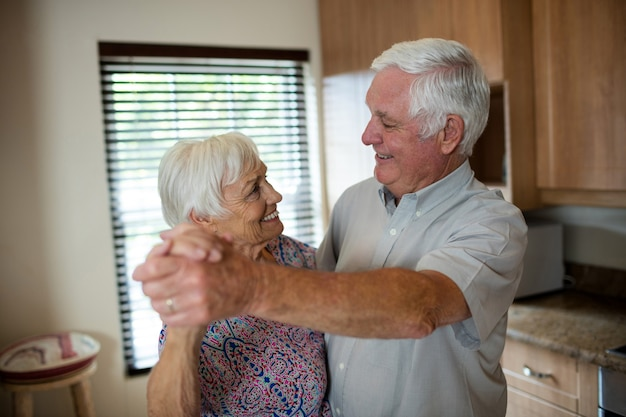 Casal de idosos dançando juntos na cozinha de casa