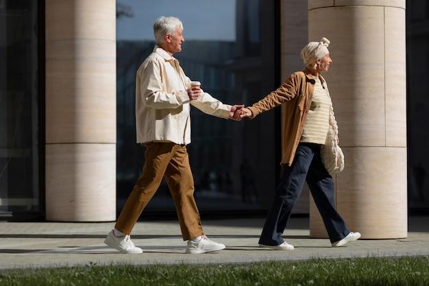 Casal de idosos de mãos dadas ao ar livre em uma caminhada pela cidade