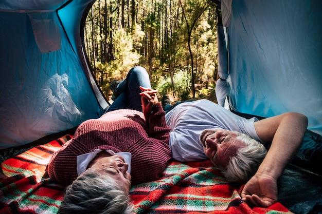 Casal de idosos descansando dentro de uma barraca em um acampamento selvagem gratuito na floresta