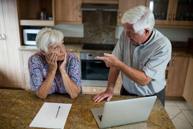 Casal de idosos discutindo na cozinha de casa