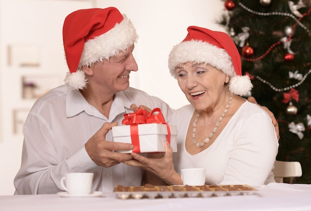 Casal de idosos divertido usando bonés de natal com presente