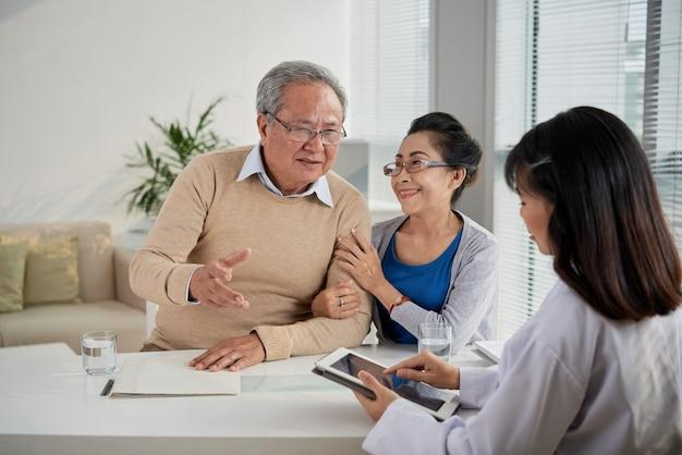 Casal de idosos dizendo preferências e expectativas da nova casa para o agente imobiliário que está enchendo ...
