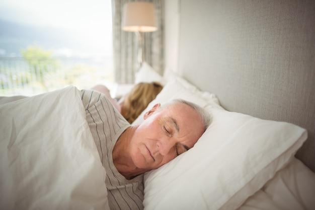 Casal de idosos dormindo na cama