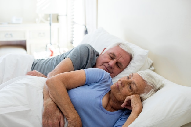 Casal de idosos dormindo no quarto de casa