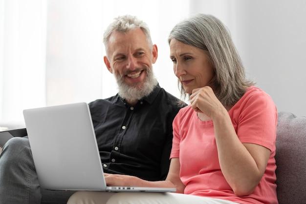 Casal de idosos em casa no sofá usando laptop