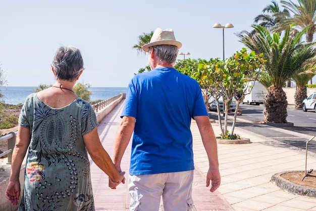 Casal de idosos em férias, caminhando e aproveitando o mar na temporada de verão - aposentadoria, atividade de lazer agradável para idosos juntos - família e novo conceito de vida