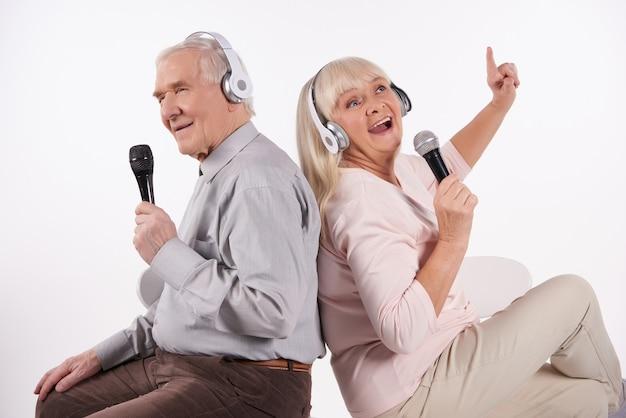 Casal de idosos em fones de ouvido está cantando karaoke.