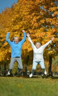 Casal de idosos em forma feliz pulando no parque de outono
