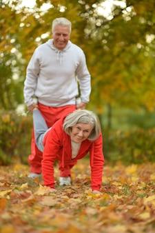 Casal de idosos em forma feliz se exercitando no parque outono