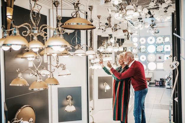 Casal de idosos em loja de iluminação doméstica fotografando o shandelier para sua casa