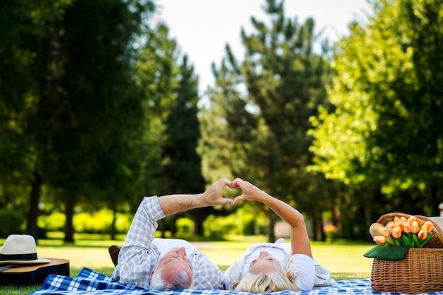 Casal de idosos fazendo coração com as mãos