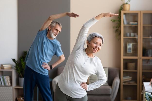 Casal de idosos fazendo exercícios em casa