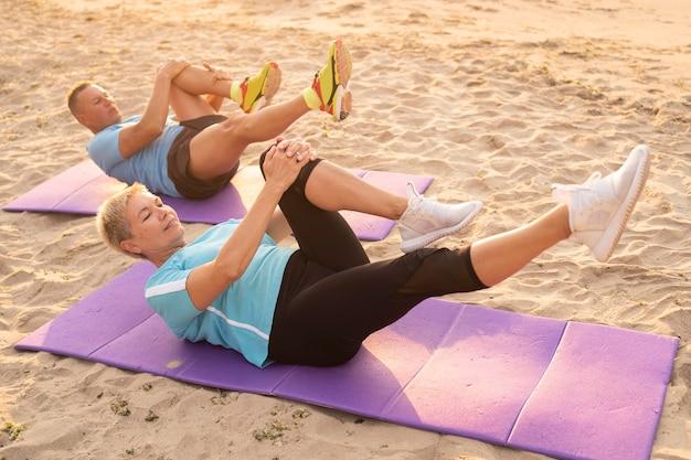 Casal de idosos fazendo exercícios juntos na praia