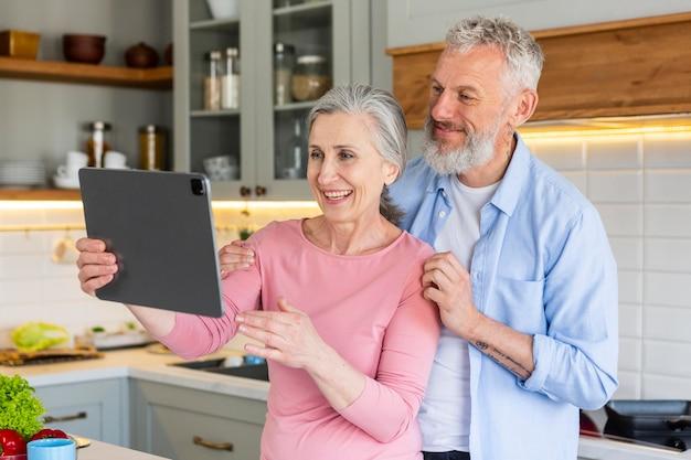 Casal de idosos feliz com tablet tiro médio