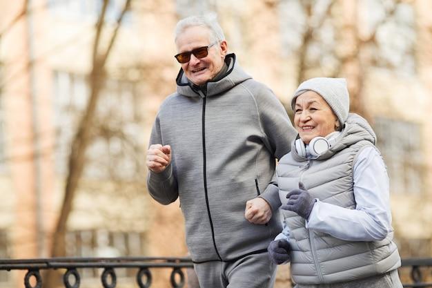 Casal de idosos feliz correndo