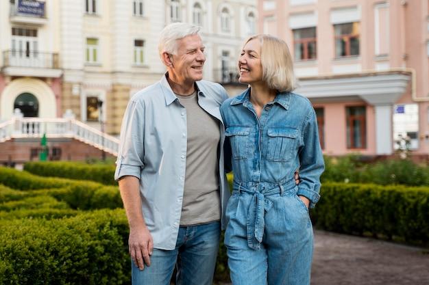 Casal de idosos feliz curtindo seu tempo na cidade enquanto se abraçava