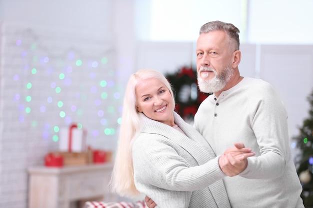 Casal de idosos feliz dançando em casa na véspera de natal