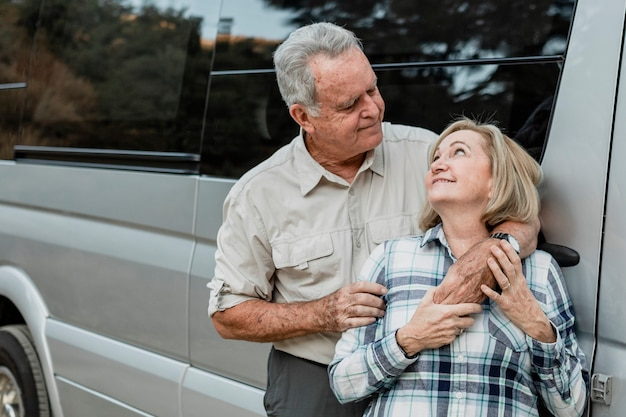 Casal de idosos feliz em pé na frente do trailer