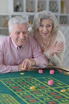 Casal de idosos feliz jogando com fichas de cassino