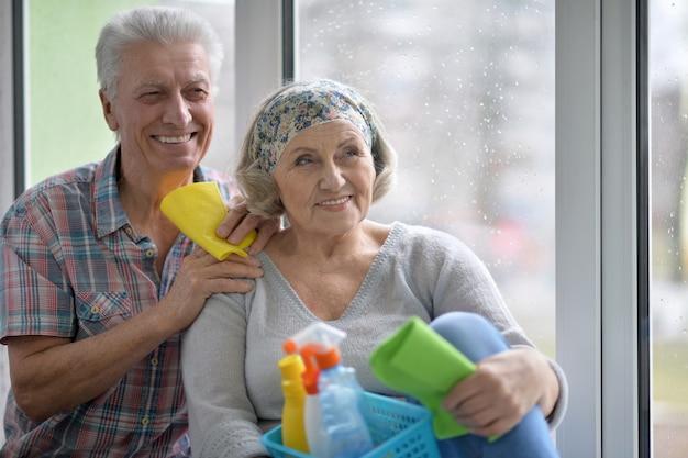 Casal de idosos feliz limpando janela em casa