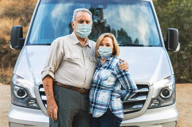 Casal de idosos feliz parado na frente de uma van de camping