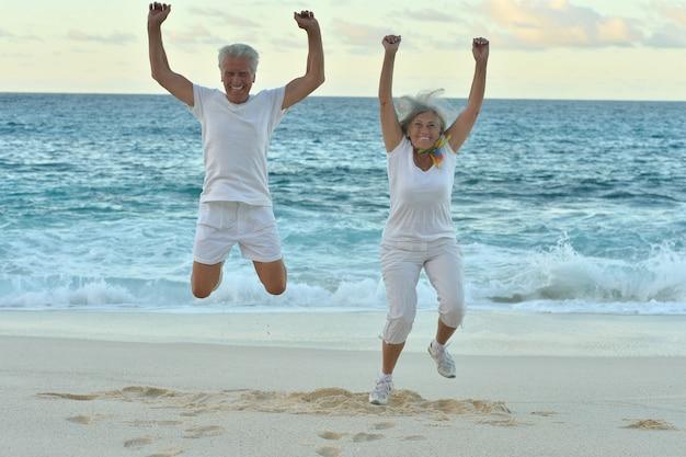 Casal de idosos feliz pulando no verão na praia