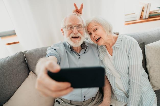 Casal de idosos feliz se divertindo e tirando fotos no celular para compartilhar online