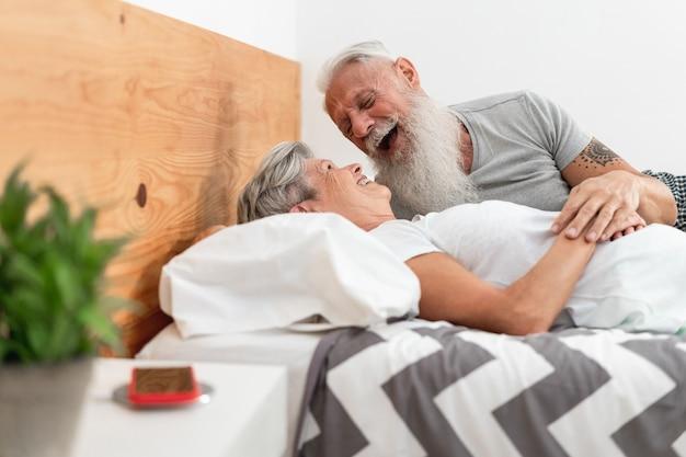 Casal de idosos feliz se divertindo na cama - foco nos rostos - foco principal no rosto do homem sênior