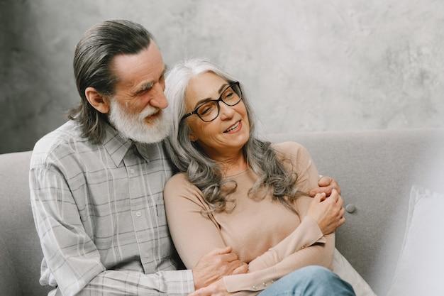 Casal de idosos feliz sentado no sofá em casa e conversando