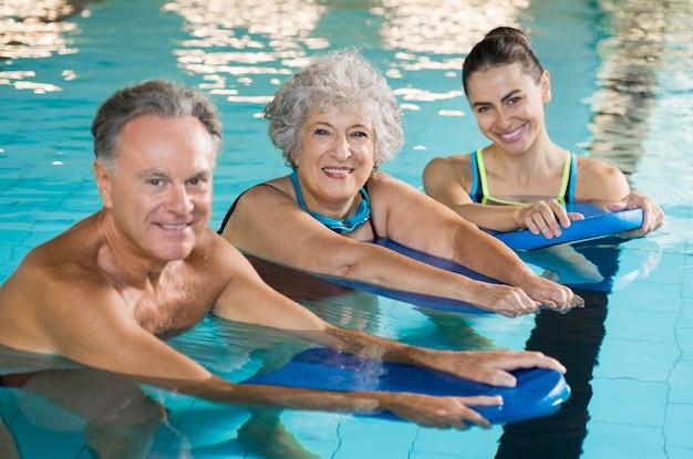 Casal de idosos feliz tendo aulas de natação com o jovem treinador