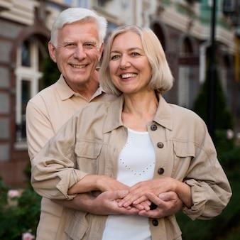 Casal de idosos felizes e sorridentes posando juntos enquanto caminhavam pela cidade