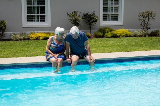 Casal de idosos felizes interagindo um com o outro à beira da piscina