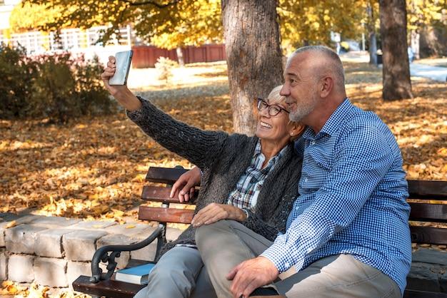 Casal de idosos felizes tirando uma selfie em um banco de um parque