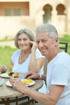 Casal de idosos felizes tomando café da manhã no café