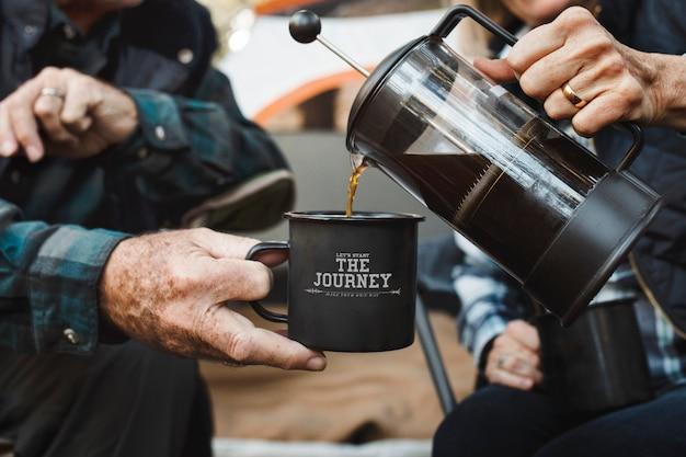 Casal de idosos felizes tomando café perto da barraca na floresta
