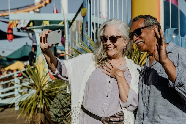 Casal de idosos fofo tirando uma selfie em um parque de diversões